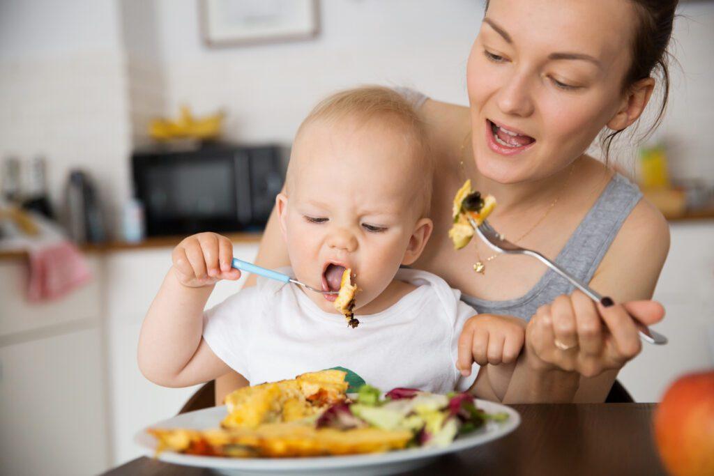 Mutter und Kind essen und kauen gemeinsam
